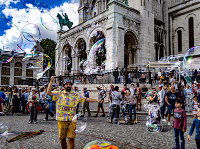 A street performer entertains with bubbles outside Sacré-Cœur Basilica, Montmartre, Paris, France.