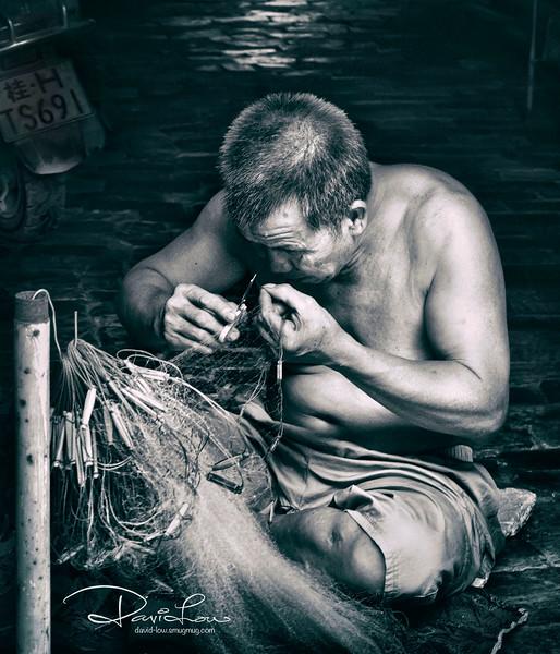 Mending the net - looked like his having serious myopia