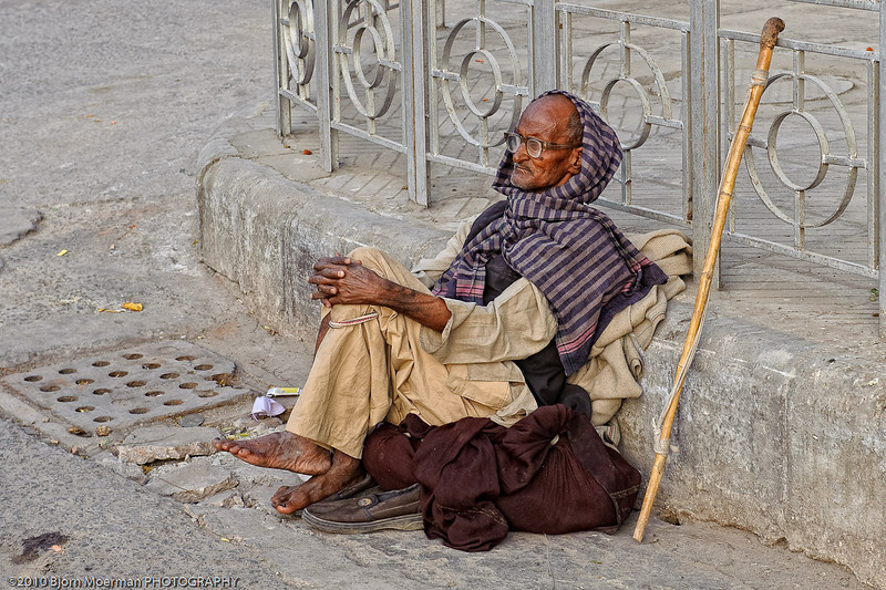 Old Indian man waiting for the time to pass at Main Bazaar, Delhi