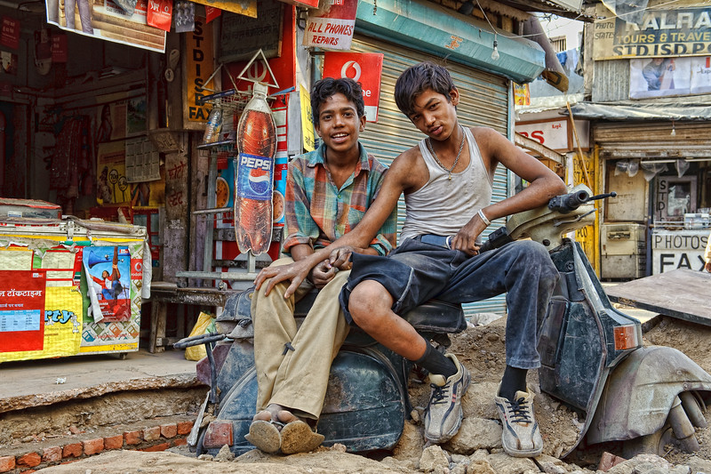 2 friends sitting on a disused scooter in Main Bazaar road, Delhi
