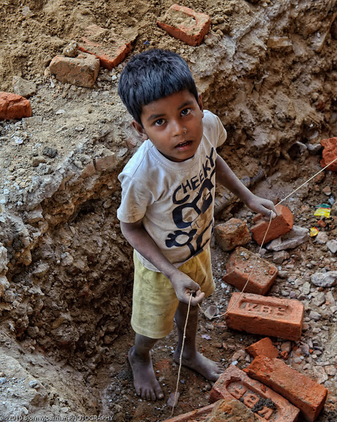 Young boy helping his family with construction work at Main Bazaar, Delhi