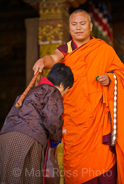 MONK WITH WHIP, BLESSING ? BOWING WOMAN