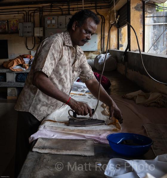 INDIAN MAN IRONING CLOTHES, DHOBI KHANA