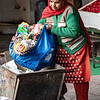 PRIMARY COLORS STUDY:  INDIAN WOMAN WITH RED SCARF, GREEN SWEATER, BLUE BAG (OF GARBAGE)