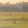 Rural Salisbury Massachusetts in Merrimack Valley, Foggy Golden Sunrise over Field and Hay Bails with Farm House