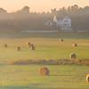 Farmland with Hay Bales and Golden Light at Sunrise in Salisbury Massachusetts