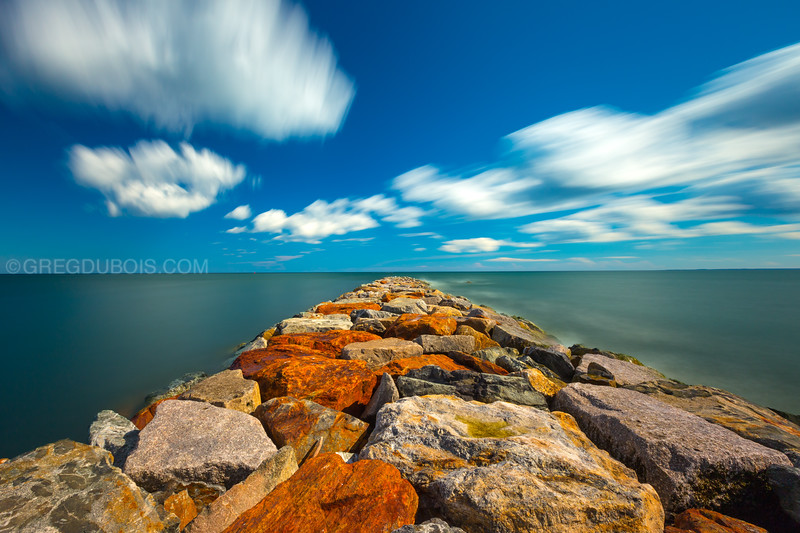 Plum Island Massachusetts USA - Daytime Long Exposure of Cumulous Clouds clearing to Atlantic Ocean over Rock Jetty