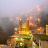 mountain village Masouleh and its mosque at night in the fog, Iran
