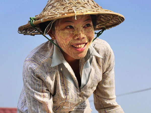 Tanaka (the yellowish cosmetic powder) smearing down a farmer's face in the sweltering heat.