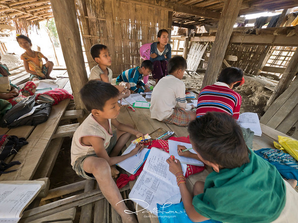 This school in Chin village has no table and chair. The floor made up of wooden planks serve as their writing place.
