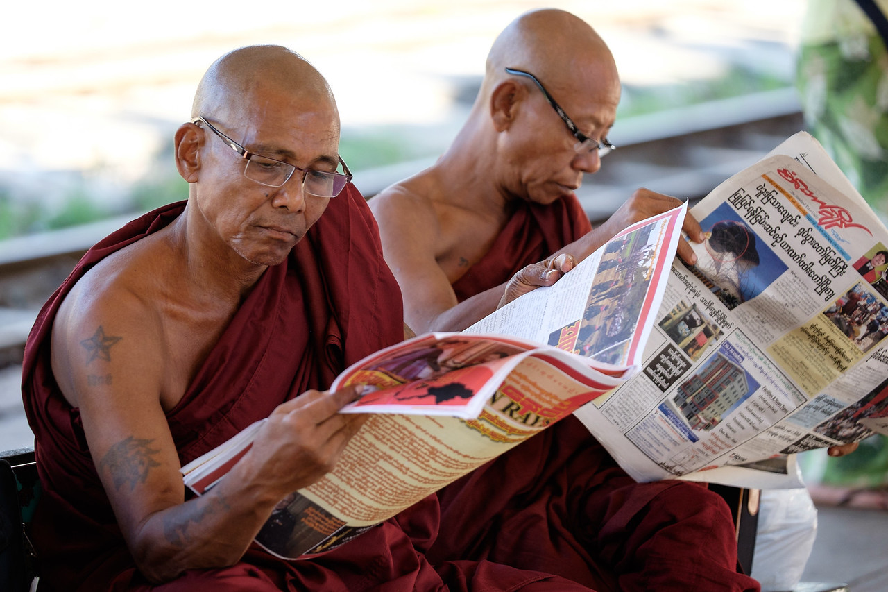 Monks reading the paper at Yangon train station