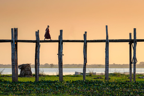Lonely monk walking U Bein bridge