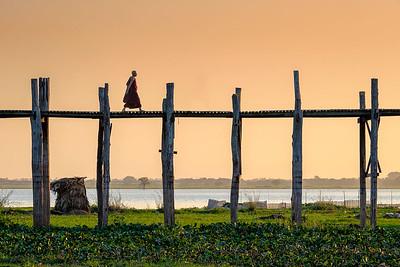 Lonely monk walking U Bein bridge