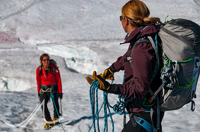 A female climber belays another woman past crevasses on the Rainbow Glacier, British Columbia, Canada.