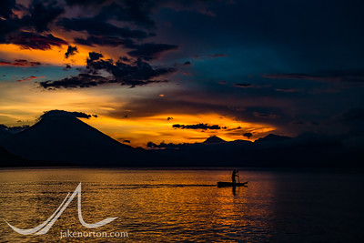A man in a handmade, wooden kayuco (kayak) paddles at sunset across the waters of Lake Atitlán near Santa Catarina Palopó, Guatemala. Volcán San Pedro rises in the distance.