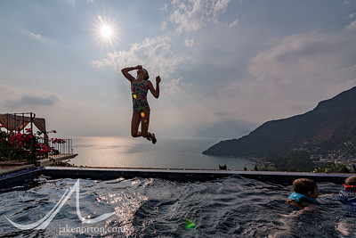 A young girl jumps into a pool looking out over Lake Atitlán, Guatemala, above the village of Santa Catarina Palopo.