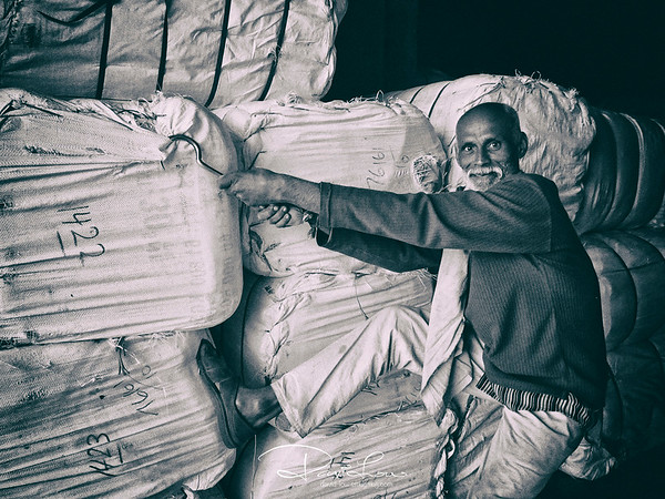 A worker transferring bale of saris