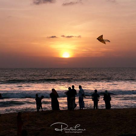 Family enjoying a breezy sunset overlooking Indian Ocean.