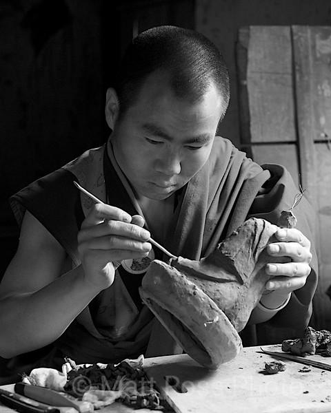 BHUTANESE MONK, CARVING A SITTING BUDDHA clay statute