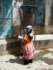 a girl getting water in Sana'a