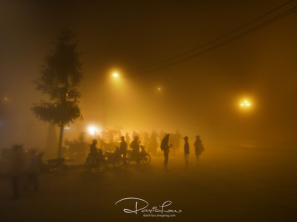 """Loafers - The street lights pierced thru' the cold and heavy fog and created """"layers"""" of people. This would make a nice monochrome but resisted the conversion. I wanted to retain the natural tawny tone of that special night that I ever experienced."""