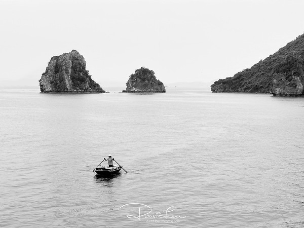 Ha Long Bay 4- One early morning as I woke up from our junk, I saw this woman paddling towards us intending to sell her provisions. I was so mesmerized by the vastness of the lake and I illustrate by isolating her to appear paddling in eternity.