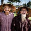 An elderly couple holding hands in the countryside near Hoi An
