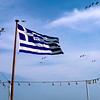 Greek flag on the Piraeus surrounded by seagulls