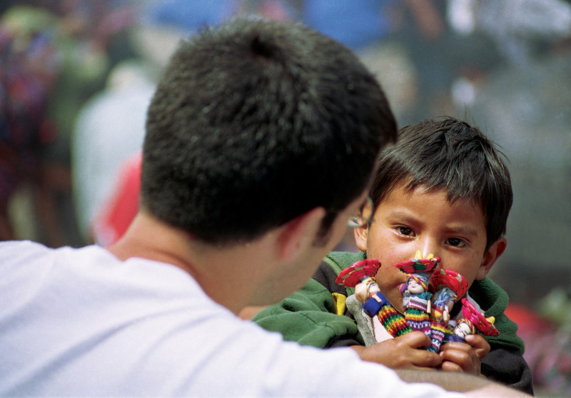 Young boy selling dolls to tourist, Chichicastenango, Guatemala