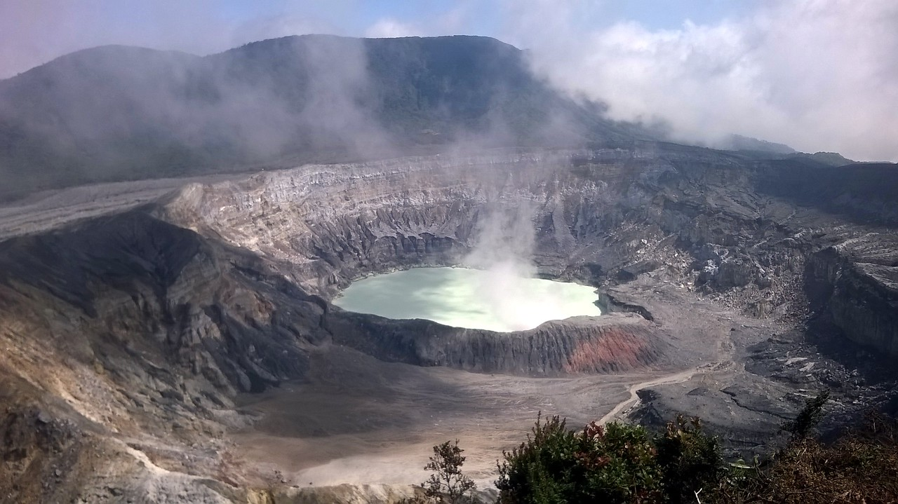 The Poas Volcano's crater. Mist rolling in and steam arising from the crater.