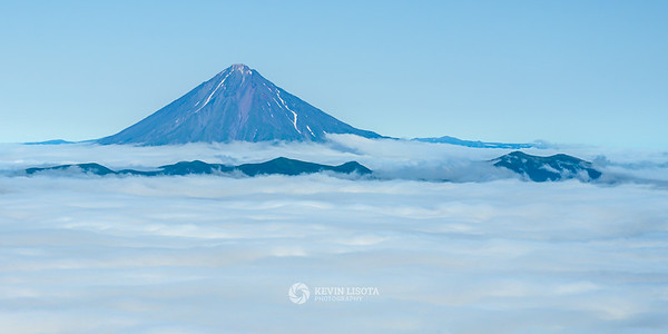 Asacha volcano rises above the clouds in Kamchatka, Russia