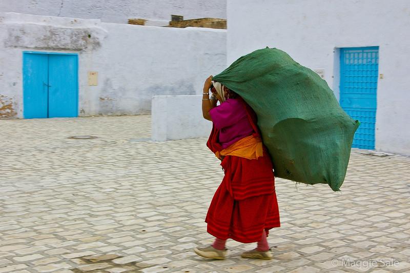 Woman carrying sack in Kairouan