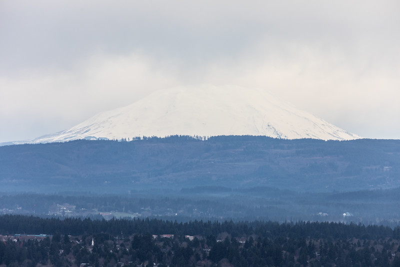 Mount St. Helens to the north, barely visible with a background of white clouds.  I was a bit surprised it could be seen from Portland but its not much further away than Mt. Hood to the east.