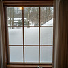 Snow atop flat roof seen through upstairs bedroom window
