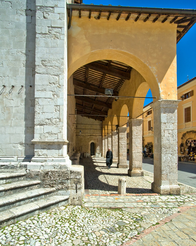 Monk walks outside church in Norcia, Umbria