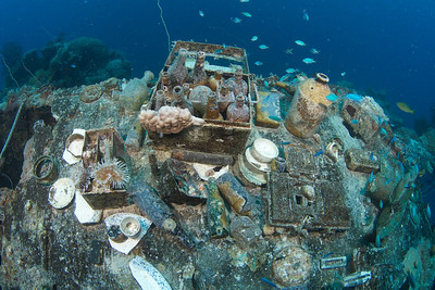 A display of artifacts on top of the Shinkoku Maru, including a medical kit, china, and beer bottles.
