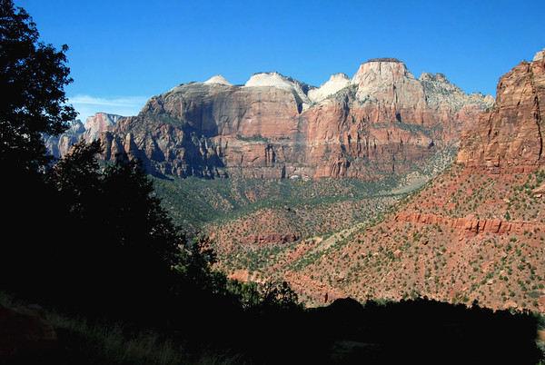"""From the lower shaded slope of Bridge Mountain - beyond the lower sunlit sandstone cliff of Mount Spry - across the mouth of Zion Canyon - to """"The Sentinel"""", """"Bee Hive Peak"""", and """"The Streaked Wall"""" directly below - with the """"Altar of Sacrifice"""" along the distal horizon - Zion National Park"""