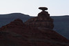Mexican Hat Rock - at dawn - with the western rim of the Nokaito Bench, along the Horizon - Navajo Nation