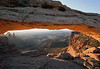 "Sunrise upon the sedimentary sandstone of Mesa Arch, along the eastern rim of ""Island in the Sky Mesa"" - down to Washer Woman Arch, and Airport Tower (directly beyond) - Buck Canyon - Canyonlands National Park"