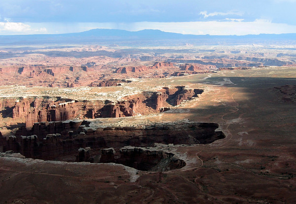 Shadow across the White Rim, at Monument Baasin - Canyonlands National Park - to a distal rain cloud shadowing the Abajo Mountains