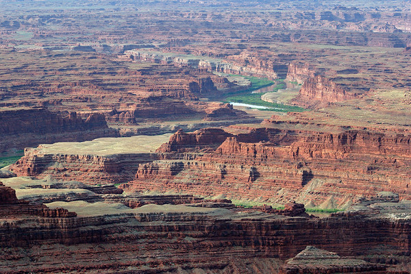 South view from Dead Horse Point - to the morning sunlight across the meandering Colorado River and riparian vegetation - among the erosion extreme of bench tops, sheer cliffs, slopes, and canyons