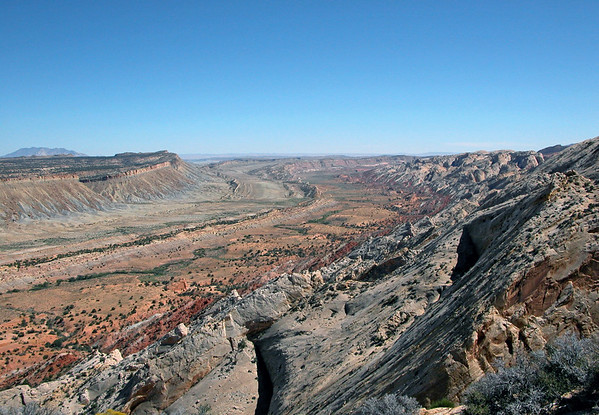 Southward down the Waterpocket Fold and Strike Valley - the fold extends 100 mi. (160 km) from the Thousand Lake Mountain (north), southward to Lake Powell - Capitol Reef National Park - Mount Pennell, rising to 11,408 ft. (3,477 m) seen along the distal horizon beyond the fold