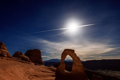 Airplane Slicing Full Moon at Delicate Arch