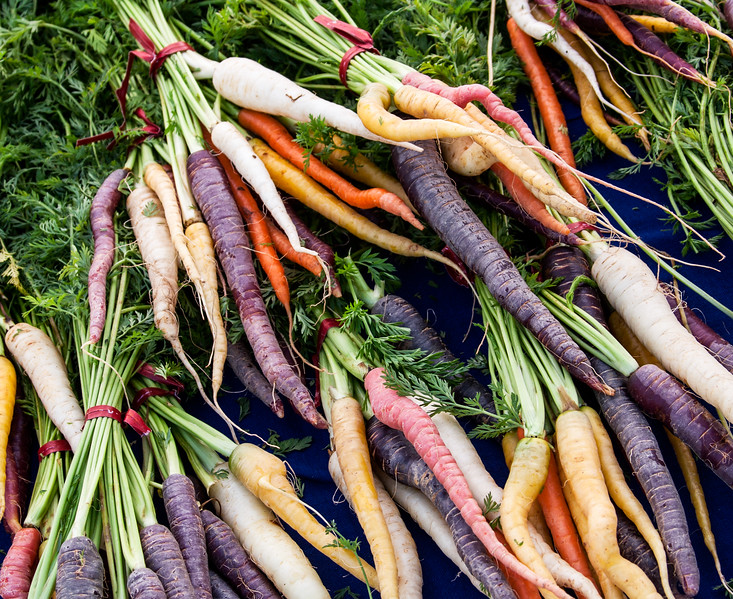 Orange, white, purple, and yellow carrots at a farmer's market