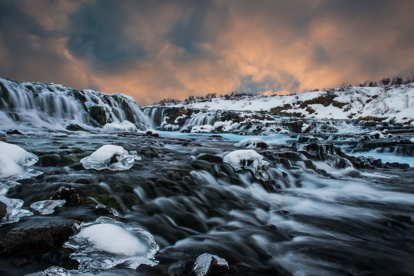 """<span class=""""AaronsSubTitle"""">Brúarfoss Waterfall Golden Circle, Iceland</span>  After leaving Gullfoss we made our way to Bruarfoss, an amazing little waterfall with some stunning cascades and blue water. It's a bit hard to find: you have to drive through a residential area and then hike a short distance to the waterfall. It was made especially hard because the roads were super icy and at one point we found ourselves stuck ... luckily Rebecca was able to maneuver us out of being stuck. We also couldn't find where to park, since the GPS location I had marked from my summer trip was now covered under snow! Eventually we were able to park and made it to the falls."""