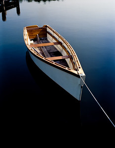 A rowboat is tied to a pier in the very early morning with the blue sky reflecting in the glassy water.