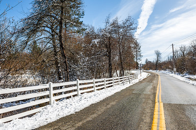 Winter landscape of a road and snow covered trees.