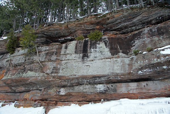Above the frozen lake waves, to the lichen cloaked sandstone cliff, along the Bayfield Peninsula shoreline, with the pine trees lining the ledge top.