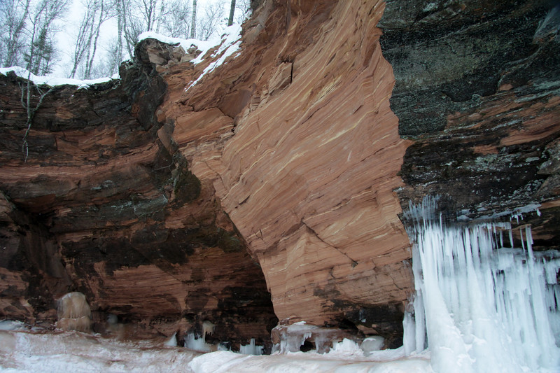 Lake wave ice meets the lichen upon the sandstone rock cliff.