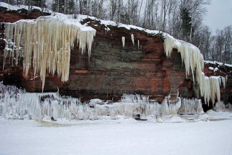 Lake Superior wave ice meets the iron oxide icicles or stream/waterfall ice, along the sedimentary sandstone rock cliff, clustered with lichen.